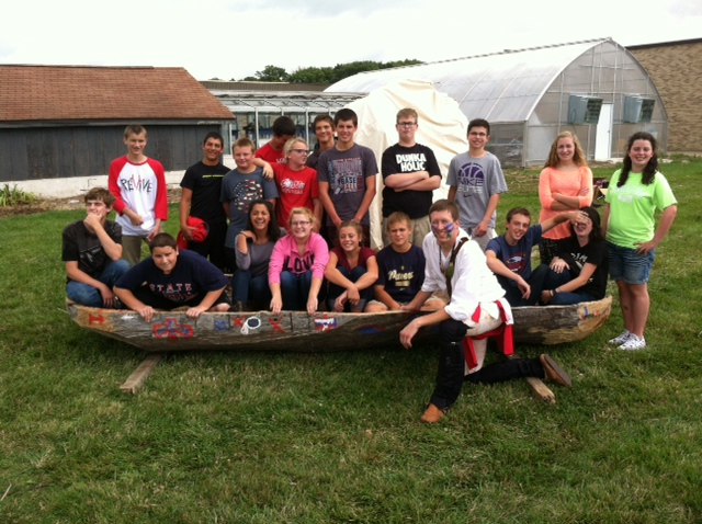 Matt Barnett and his students gather around the hand-carved canoe he made.